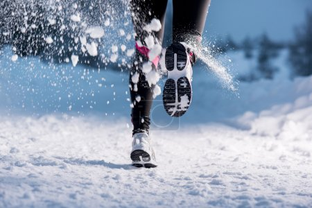 Photo for Athlete woman is running during winter training outside in cold snow weather. - Royalty Free Image