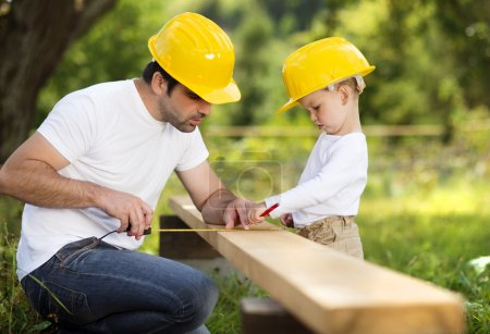 Photo for Little son helping his father with building work - Royalty Free Image