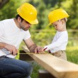 Little son helping his father with building work...