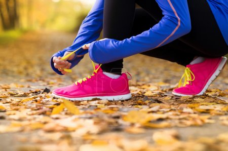 Photo for Close up of feet of a runner running in autumn leaves training exercise - Royalty Free Image