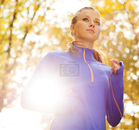 Bautiful running woman jogging in autumn nature...
