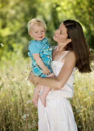 Photo for Beautiful mother holding her son on hands - Royalty Free Image