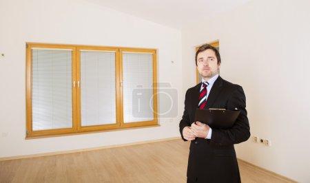 Photo pour Immobilienmakler steht in der neuen leeren Haus. - image libre de droit