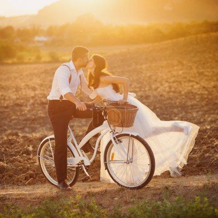 Photo pour Beau portrait de mariage de mariée et marié avec vélo blanc - image libre de droit