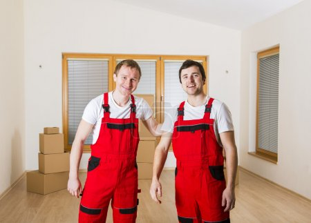 Photo for Movers in new house with lot of boxes behind them. - Royalty Free Image