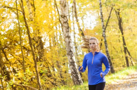 Photo for Active and sporty woman runner is exercising in colorful autumn nature - Royalty Free Image