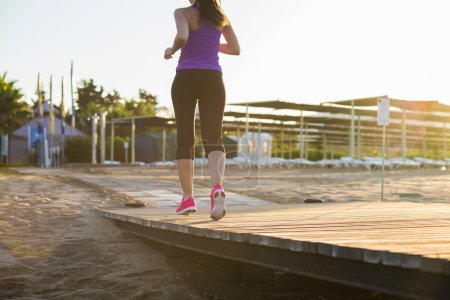 Photo for Running woman. Female runner jogging during outdoor workout on pier. Feet detail. - Royalty Free Image