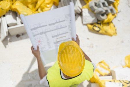 Photo pour Constructeurs d'ingénieur en sécurité gilet avec blueprint au chantier de construction - image libre de droit