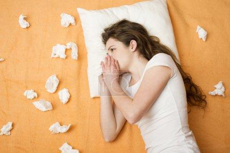 Photo pour Femme malade couchée au lit avec le rhume et la grippe. Elle se mouche. . - image libre de droit