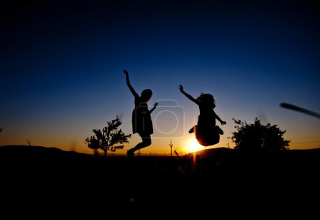 Silhouettes of happy girls