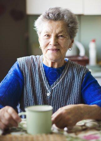 Photo pour Vieille femme boit du thé dans sa cuisine de style campagnard - image libre de droit