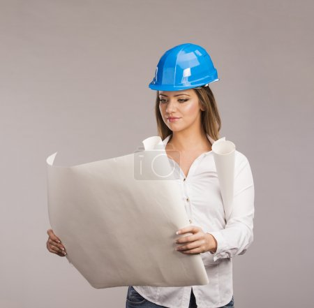 Photo for Portrait of Young woman architect with blue hard hat and paper plans, isolated on white background - Royalty Free Image