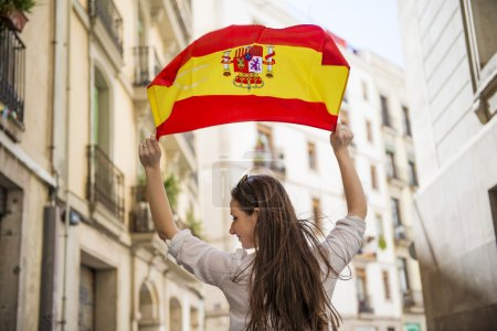 Photo for Happy woman tourist is walking in the city street of Barcelon with spanish flag. - Royalty Free Image