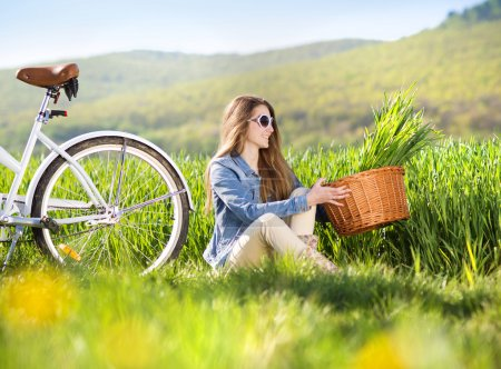 Photo for Pretty young girl with bike in green field - Royalty Free Image