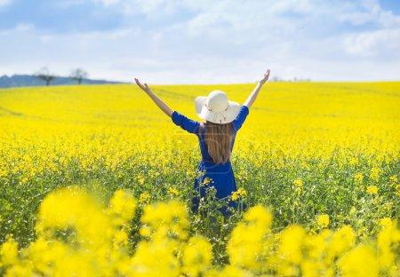 Photo pour Heureuse jeune fille en robe bleue et chapeau de paille profiter de temps libre dans le champ de colza jaune - image libre de droit