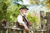 Farmer standing  by the lath fence