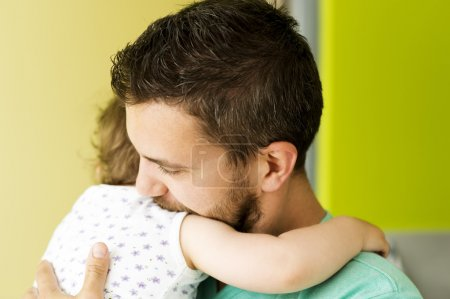 Photo pour Portrait intérieur du jeune père étreindre sa petite fille - image libre de droit