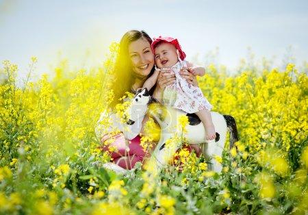 Photo pour Heureuse jeune maman s'amuser avec sa petite fille dans la nature de l'été - image libre de droit