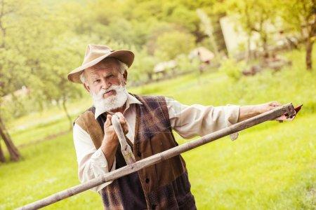 Bauer bereitet seine Sense vor
