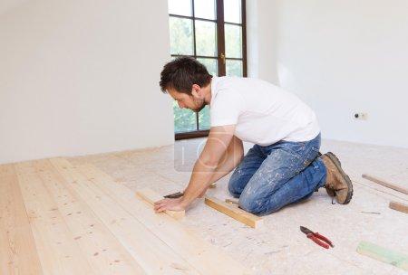 Handyman installing wooden floor