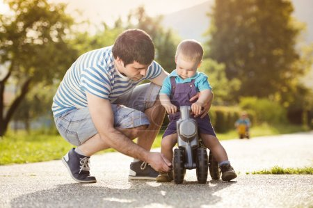 Young father with his little son on motorbike in green sunny park