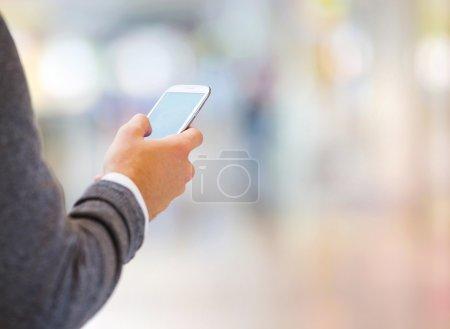 Photo pour Beau jeune homme dans le centre commercial en utilisant le téléphone mobile - image libre de droit