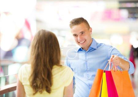 Photo pour Heureux jeune couple avec des sacs dans le centre commercial - image libre de droit