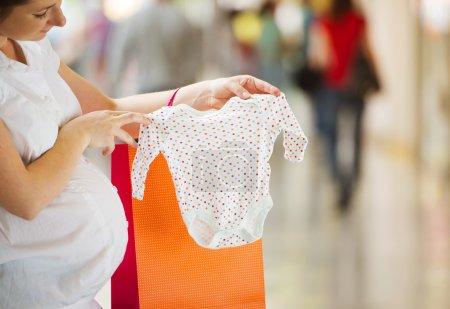 Photo pour Jeune femme enceinte regardant de nouveaux vêtements de bébé dans le centre commercial - image libre de droit