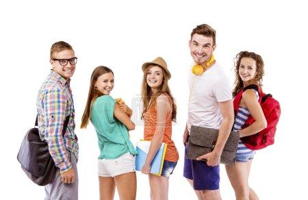 Photo pour Groupe de jeunes adolescents heureux debout et souriants avec des livres et des sacs isolés sur fond blanc . - image libre de droit