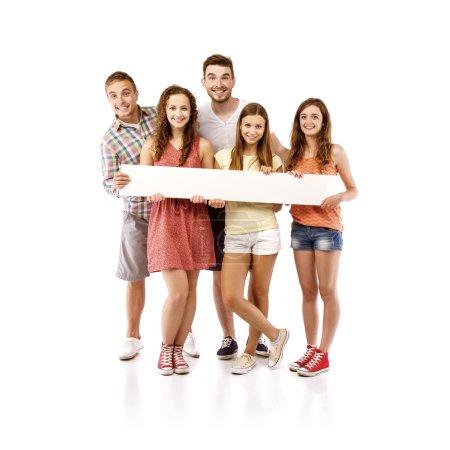 Photo pour Groupe de jeunes étudiants adolescents heureux debout et souriant avec panneau blanc isolé sur fond blanc . - image libre de droit