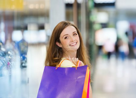 Photo for Happy young girl with bags in shopping mall - Royalty Free Image