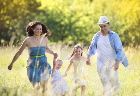 Family running on sunny meadow