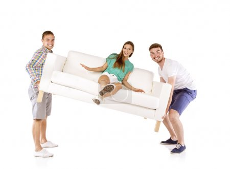Men lifting sofa with woman on it