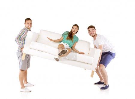 Photo pour Deux jeunes hommes beau canapé de levage avec belle jeune femme assis sur elle, isolé sur fond blanc - image libre de droit