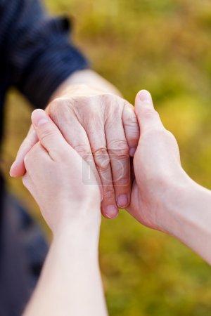 Photo pour Jeune médecin tenir les mains âgées - image libre de droit