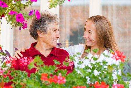 Photo pour Heureuse femme âgée et son assistant serviable - image libre de droit