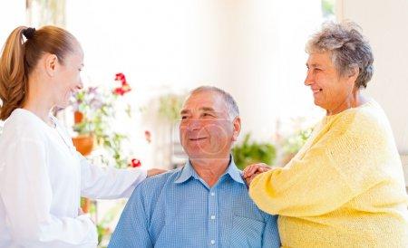 Photo pour Heureux couple âgé parlant avec leur soignant - image libre de droit