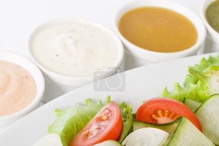 Photo pour Salade et vinaigrettes - Salade avec concombre, tomate, oignons et laitue servie avec quatre sauces . - image libre de droit