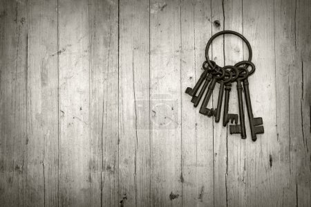Photo for Bunch of old keys on wooden background black and white - Royalty Free Image