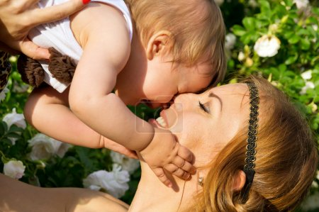 Portrait of happy mother and child on a background of flowers