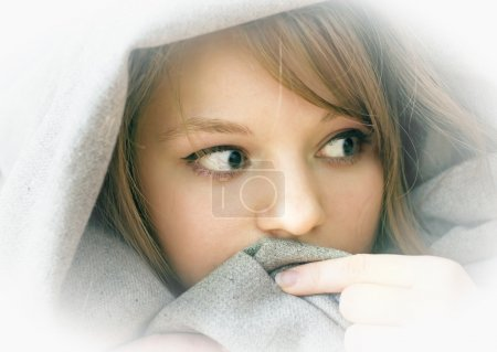 Photo for Frightened girl lying under a blanket, in the house - Royalty Free Image