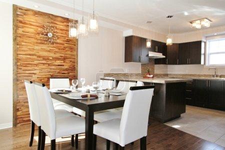 Photo pour Cuisine en bois foncé et salle à manger moderne avec panneau arrière en bandes de bois horizontales - image libre de droit