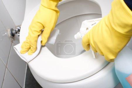 Photo pour Mains sur les gants jaunes nettoyage d'un WC - image libre de droit