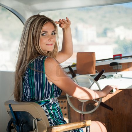 Young, beautiful woman operates the yacht