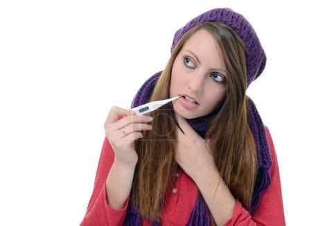Photo pour Mignon jeune femme à l'aide d'un thermomètre dans sa bouche - image libre de droit