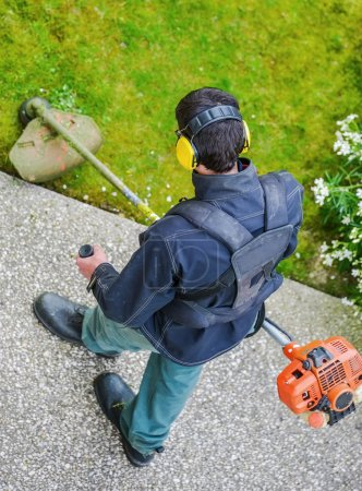 Photo pour Jardinier à l'aide d'une tondeuse à cordes dans un parc - image libre de droit