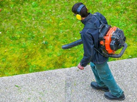 Photo pour Jardinier utilisant un ventilateur à gaz dans un parc - image libre de droit
