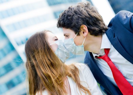 Lovers workers kissing with protective face mask against polluti