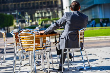 Photo pour Vue arrière de l'homme d'affaires moderne sur la terrasse du café - image libre de droit
