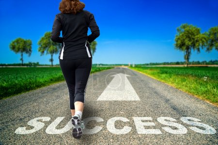 Running woman and Success word painted on asphalt